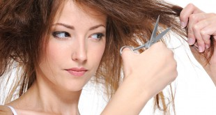 young woman cutting her backcombing brunette hair - close-up